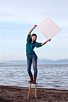 Young woman holding a blank sign, in front of the Great Salt Lake.
