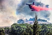 Airplane drops fire retardant on homes in Utah neighborhood.