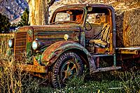 Front of an old Mack Truck abandoned in a field at the base of the Wasatch Mountains