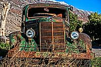 Old antique Mac Truck, rusted, abandoned, sitting in the light of a setting sun.