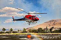 Helicopter lifts up water in a bucket to fight fire, South Jordan, Utah, USA