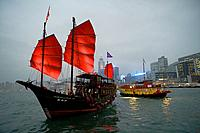 Two boats pass each other at night on Victoria Harbour, Hong Kong - the iconic Aqua Luna with Red Sails and a Wing On Travel boat