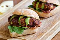 Cajun chicken burgers with spinach, avocado and grilled bacon.