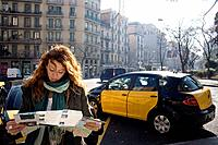 Barcelona, Spain. Young woman reading street map.