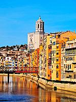 Colorful houses and the cathedral of Girona reflecting in the Onyar River.