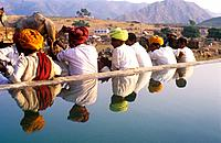 Colourful turbans reflected in a water tank , Pushkar Camel Fair , Rajasthan , India.