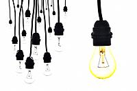 A yellow light bulb next to a number of light bulbs hanging on white.