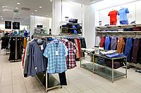 Shop interior with mannequin, dummy. Shelf, rack and clothes hanging in retail store.