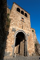 A Dog Stands at the Gate of Santa Maria. Civita di Bagnoregio. Viterbo district. Lazio. Italy.