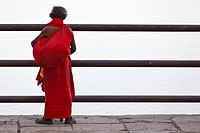 Man in red Frock looking onto the River Ganges in Varanasi, India