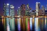 The Central Business District by night. In the foreground the water of Marina bay. Singapore.