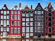 Charming, old apartment buildings on the edge of one of the many canals running through the old city in Amsterdam, Netherlands.
