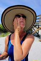 a senior woman applying sunscreen to her face at a beach