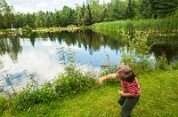 A young boy hurls a stone into a placid pond, Quebec, Canada