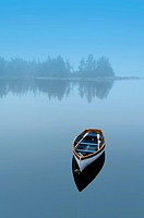 A single boat is reflected in a placid blue sea, Halifax, Nova Scotia, Canada