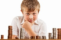 A young boy of 10 counts his money and stacks it up.
