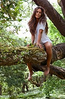 Fashion portrait of young sensual lady on tree.
