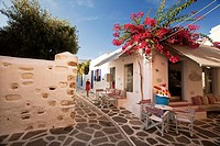 Woman walking through the alleys of Parikia, Paros, Cyclades Islands, Greek Islands, Greece, Europe.