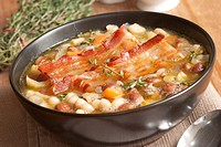 Delicious Tuscan soup with crispy bacon and beans.