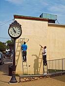 Workmen prepare to install a piece of art on an exterior wall in downtown Vineyard Haven, Martha's Vineyard, Massachussets.