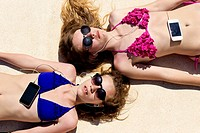 Two teenage girls lying in the sun listening to music on their mobile phones.