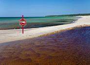 Life bouy, life belt hanging on post. Sandy beach in Vääna-Jõesuu river mouth in Estonia. Baltic sea.