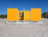 Yellow dressing cabin, changing cubicle number 22 on empty Pärnu beach in Estonia. Changing room.