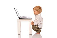 Young boy looking at a laptop on a stool. Isolated on white background.