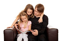 Family reading a story before going sleeping in a brown designed armchair. Isolated on white background.