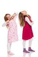 Two funny children with long hair making faces. Isolated on white background.