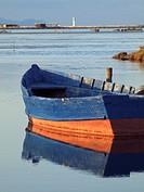 Fishing boat, mussel breeding sites and lighthouse at Fangar Bay. Ebro River Delta Natural Park, Tarragona province, Catalonia, Spain.