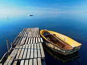Pallet pier and small fishing boat at Alfacs Bay. Ebro River Delta Natural Park, Tarragona province, Catalonia, Spain.