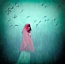 Woman wearing red cloak walking in to dense fog.