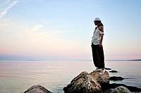 Woman standing on rock watching sunset, Island Pag, Croatia, Europe.