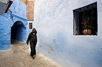 Man dressed traditionally walking in a street in the Chefchaouen Old Town Medina, Morocco.