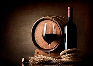 Bottle of red wine, grapes and wooden barrel.