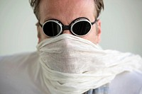 Man with sunglasses and a scarf cover his face.