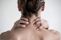 Worried woman holding her neck with her hands.
