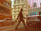 Net against man crossing the road in in New York, New York.