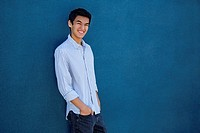 Teenager standing in front of a blue wall.