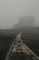 Old house and road with white lines in the mist, Guadarrama National Park, Region of Madrid, Spain