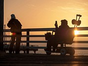 Silhouette of people looking at sea from pier, Pismo Beach, California.
