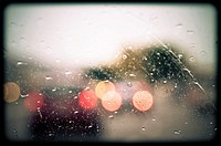 Rain drops on windshield. Blurred view of cars.