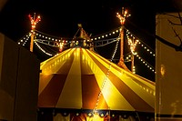 An illuminated big top at night with the nigh sky at background.