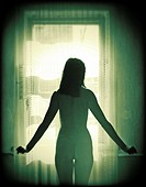 Nude young woman standing at a window.