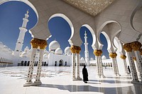Woman wearing an abaya in the mosque courtyard. United Arab Emirates, UAE, Abu Dhabi, Sheikh Zayed Grand Mosque.