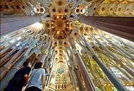 Couple admiring the ceiling of the Sagrada Familia Temple by Antoni Gaudi. Barcelona, Spain.