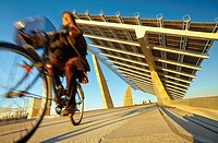 """Cyclist passing by the solar panels at the Forum Esplanade, designed by architects Elias Torres and Jose Antonio Martinez Lapena for the """"""""Forum Barce..."""