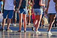 Detail of young legs in shorts in a street, summer. Barcelona, Catalonia, Spain.