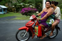 Rarotonga Island. Cook Island. Polynesia. South Pacific Ocean. Two obese people drive a motorcycle on a road on the island of Rarotonga. Obesity in th...